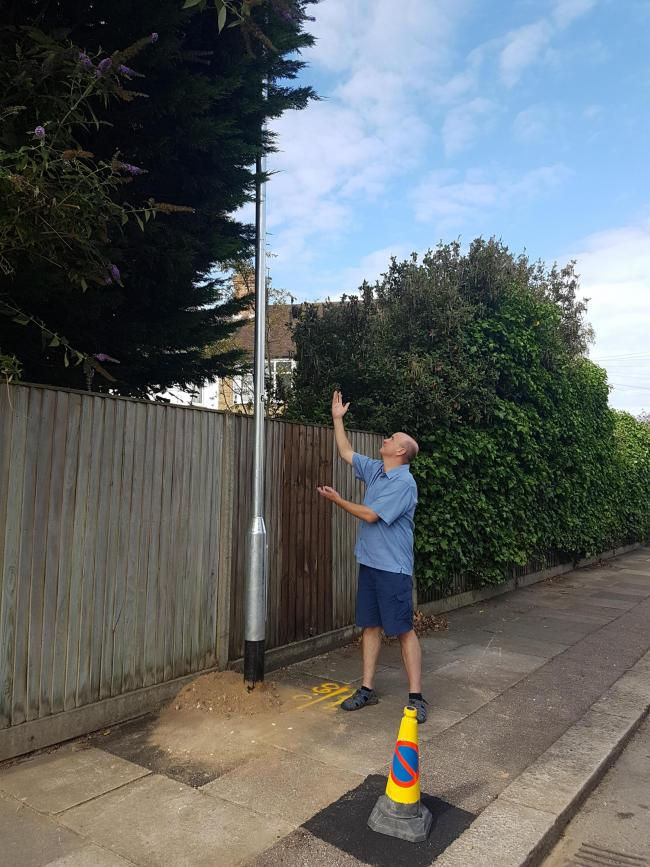 Councillor Tim Williams looking up at the new lamppost