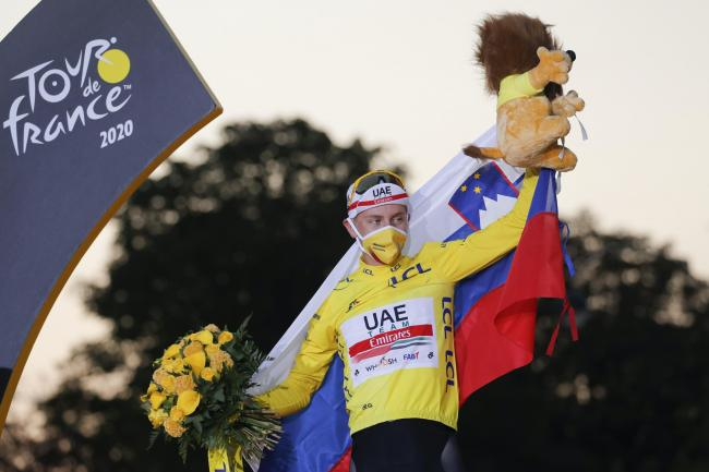Tadej Pogacar celebrates his Tour de France victory on the podium in Paris