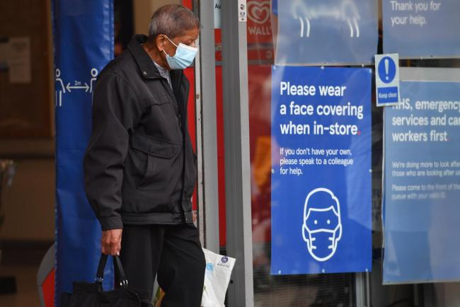 A man leaves a shop wearing a face mask. (stock image). Credit: PA