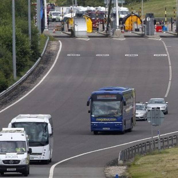 A Megabus coach is escorted away from the scene on the M6 toll motorway near Weeford, Staffordshire