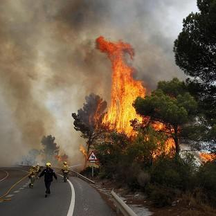 Hillingdon Times: Firefighters work to control a raging forest fire as trees are engulfed in flames next to a road in Ojen, southern Spain (AP)