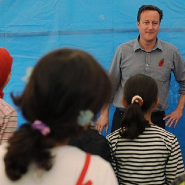 Hillingdon Times: Prime Minister David Cameron meets children and teachers in a classroom at the Za'atri refugee camp near the Syrian - Jordanian border