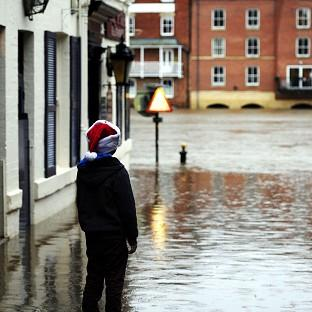 A young Christmas shopper looks at flood water in York city centre as heavy rain continues to cause problems across the UK