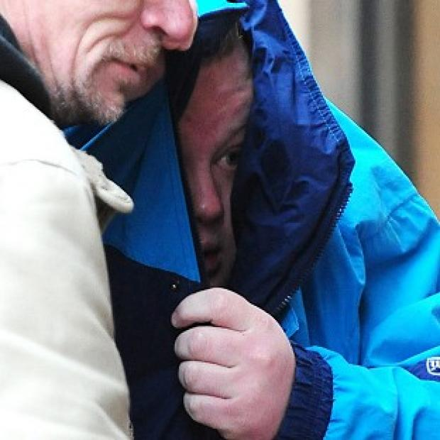Liam Ferrar, in the blue coat, outside Leicester Magistrates Court where he admitted leaving a pig's head outside a community centre