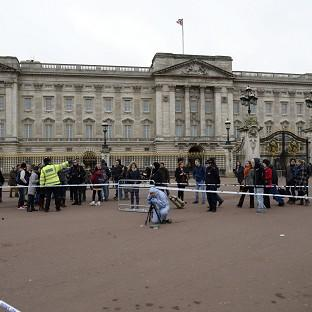 A crime officer documents evidence between the Queen Victoria Memorial and Buckingham Palace where police subdued a suspect