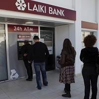 People queue to use an ATM machine outside a Cyprus bank after learning their deposit accounts are to be taxed (AP)
