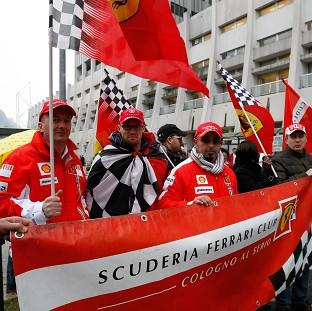 Hillingdon Times: Supporters of Michael Schumacher hold Ferrari flags to mark his 45th birthday in front of the Grenoble hospital where he is being treated. (AP)