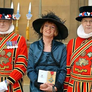 Artist Grayson Perry holds his CBE presented to him by the Prince of Wales during an investiture ceremony