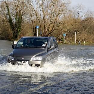 A car drives through flood water as the River Thames burst its bank and flo