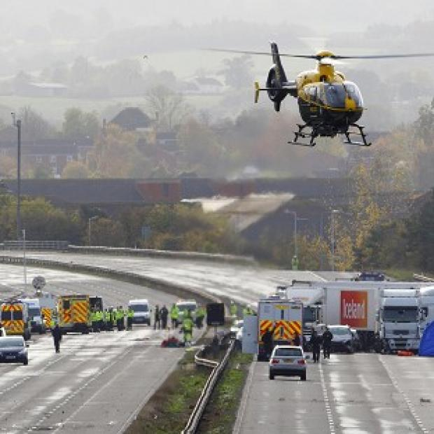 Hillingdon Times: Emergency services work at the scene on the M5 motorway close to Taunton following the pile-up