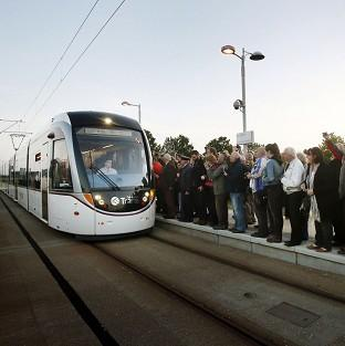 Hillingdon Times: The first paying passengers wait to board a tram at the Gyle shopping centre in Edinburgh