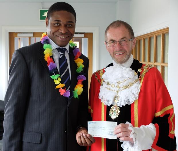 Cheque it out: the mayor hands his cheque to consultant Jide Menakaya