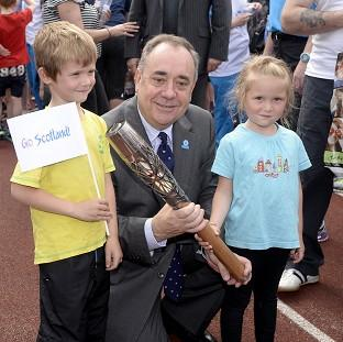 Scotland's First Minister Alex Salmond with Craig Burns (aged seven) and Marilee Burns (aged five) and the Glasgow 2014 Queen's Baton at Meadowbank Stadium in Edinburgh. (Ben Birchall for Glasgow 2014)