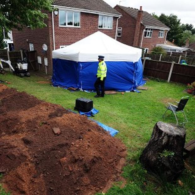Hillingdon Times: Police in the garden of a house in Mansfield, where the remains of William and Patricia Wycherley were discovered