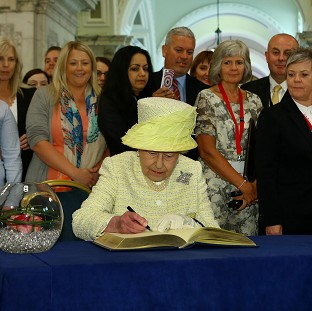 The Queen signs a book following her visit to the Belfast City Hall