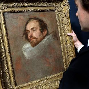 A member of Christie's staff looking at a portrait by Sir Anthony Van Dyck, which failed to sell at auction.
