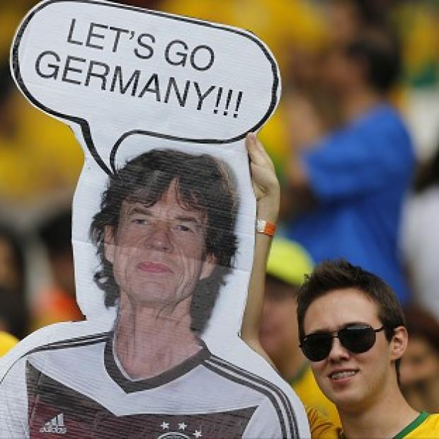 Hillingdon Times: Brazil fans hold a poster depicting Rolling Stones singer Sir Mick Jagger wearing a Germany shirt before the World Cup semifinal match between Brazil and Germany (AP)