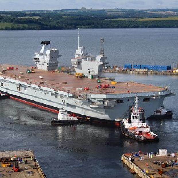 Hillingdon Times: HMS Queen Elizabeth, the largest warship ever built in the UK, during her 'float out' of the dock at the Rosyth Dockyard in Fife, in which she was assembled for the first time. (BAE Systems/PA)