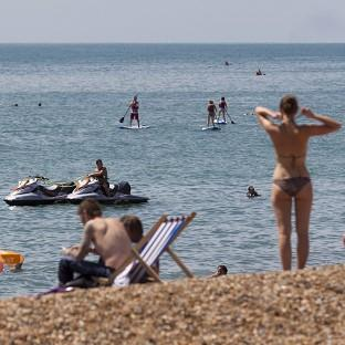 People flock to the beach in Brighton, East Sussex, as temperatures soar