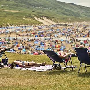 People relax in sunny weather at Woolacombe, North