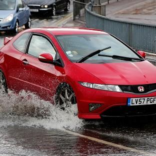 Cars pass through a flash flood following a heavy rain shower in Maidstone