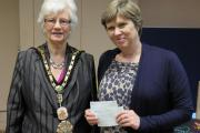 Busy year: the mayor hands a bumper donation to Melanie Burfitt, of Michael Sobell